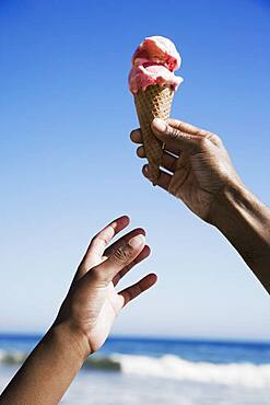 African girl reaching for ice cream cone