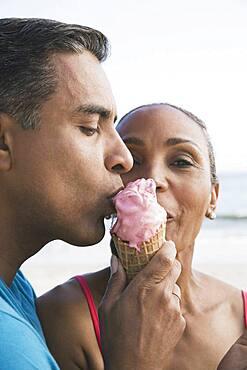 Multi-ethnic couple eating ice cream cone