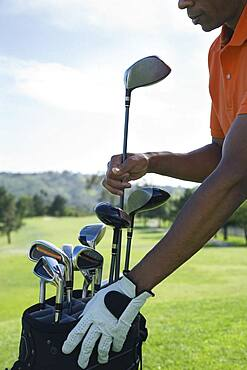 African man taking golf club from bag