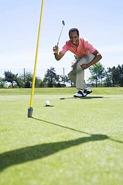 African man playing golf