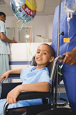 African boy being pushed in wheelchair in hospital