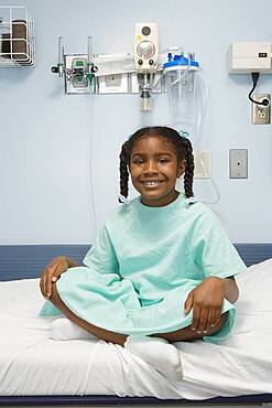 Young African girl sitting in hospital bed smiling