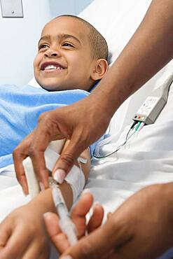African boy receiving IV medication in hospital bed