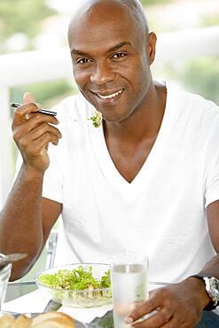 African American man eating salad