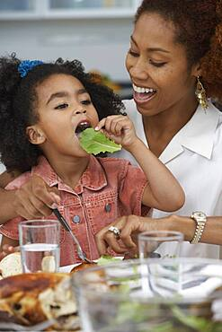 Young girl eating a leaf of lettuce at the dinner table