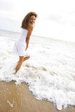 African woman standing in ocean surf