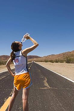 Mixed Race female runner drinking water