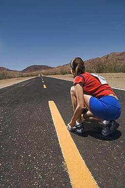 Mixed Race woman tying running shoe