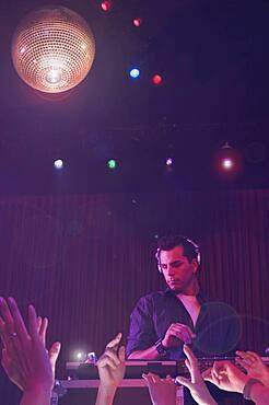 Hispanic dj playing at nightclub
