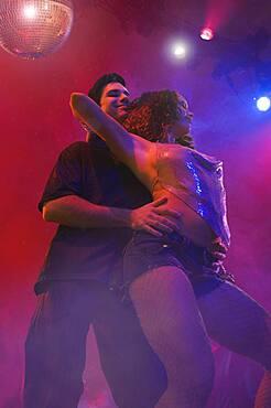 Multi-ethnic couple dancing at nightclub