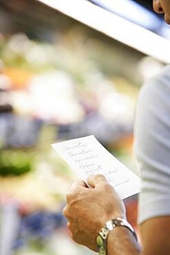 Hispanic man reading grocery list
