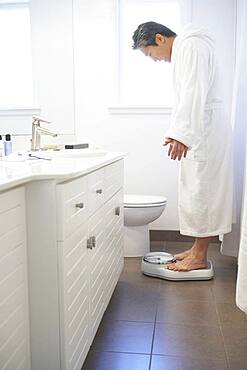 Asian man standing on bathroom scale