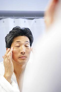 Asian man rubbing face in mirror