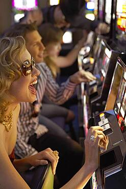 Young woman playing the slot machines in a casino
