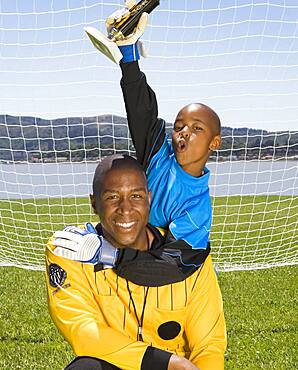 African boy and coach with soccer trophy