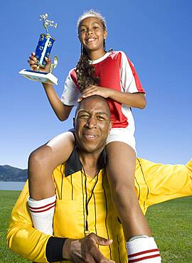 Mixed Race girl on soccer coach's shoulders