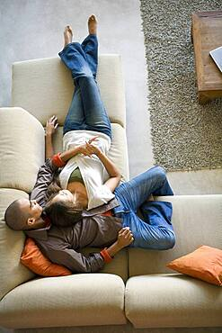 African American couple laying on sofa