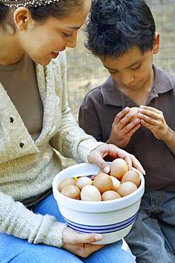 Hispanic mother and son with bowl of eggs