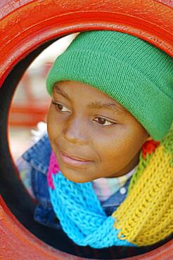 African girl leaning head through tire swing
