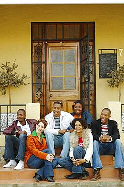 Multi-ethnic friends sitting on porch steps