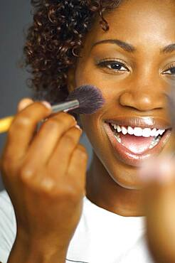 Close up of African woman applying make up