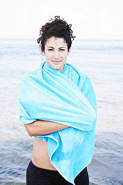 Woman wrapped in towel at beach