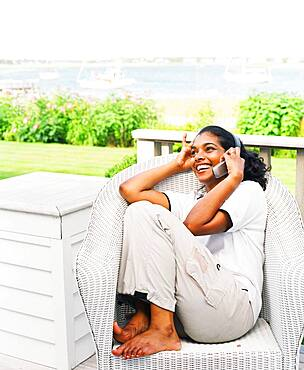 Young woman using cell phone on porch