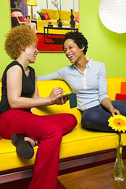 African women laughing on sofa