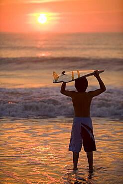 Asian boy holding surfboard at beach