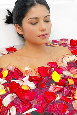Hispanic woman with eyes closed in bath of flower petals