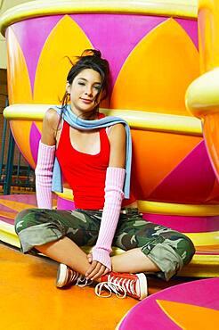 Hispanic teenage girl sitting next to carnival ride