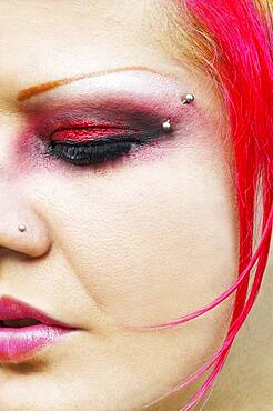 Close up of Hispanic woman with vibrant make-up and facial piercings