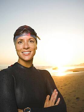 Hispanic woman wearing wetsuit and goggles