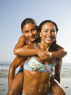Hispanic mother giving daughter piggyback ride