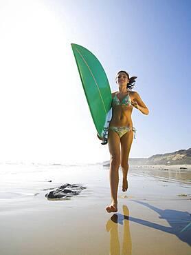 Hispanic girl running with surfboard