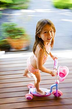 Asian girl riding foot powered scooter