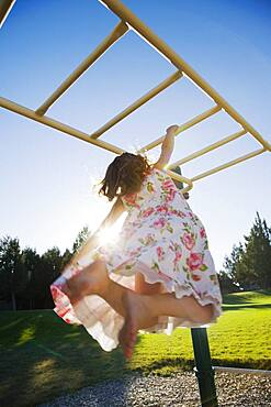 Asian girl hanging on play structure
