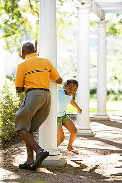 African American grandfather and granddaughter playing outdoors