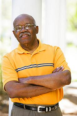 Senior African American man leaning on post outdoors