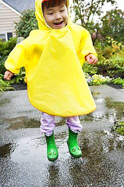 Young boy jumping in rain with rubber boots and raincoat on