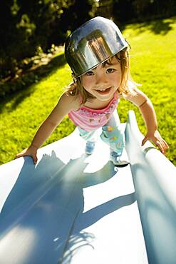 Portrait of girl climbing slide with bowl on head