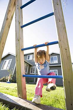 Young girl playing on play structure in back yard