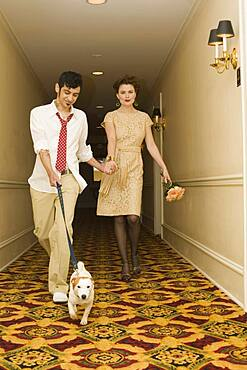 Young coupled dressed up walking down hotel hallway with dog
