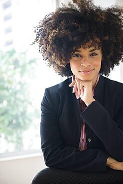 Mixed race businesswoman sitting near window