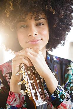 Mixed race musician holding guitar