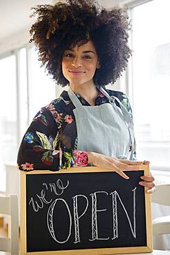 Mixed race woman holding open sign in cafe