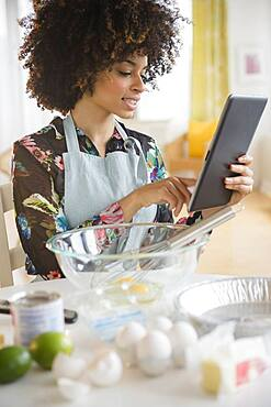 Mixed race woman baking with recipe on digital tablet