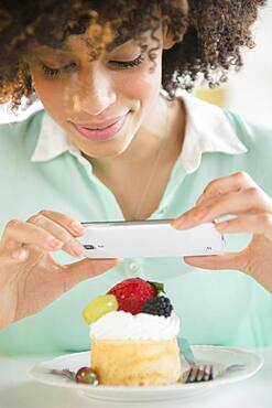 Mixed race woman taking cell phone photograph of dessert