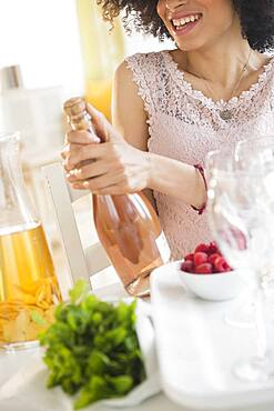 Mixed race woman opening bottle of wine