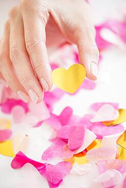 Mixed race woman holding confetti hearts